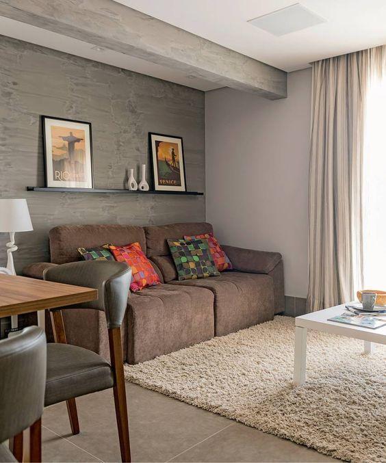 Sala somente com um sofá cinza escuro e almofadas coloridas, prateleira com quadros e enfeites, mesa de centro branca e mesa de madeira com cadeiras cinza.