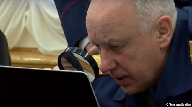 Глава Следственного комитета Александр Бастрыкин с лупой у экрана компьютера.