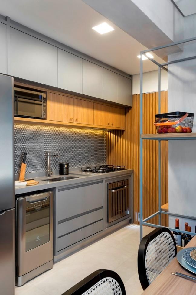 Cozinha em estilo moderno com pastilhas cinza na parede da pia, armários cinza e piso em tom neutro