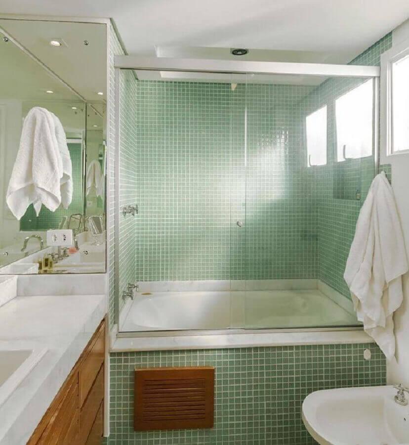 Banheiro com área do box revestida de pastilhas de cerâmica, banheira, box de vidro, gabinete de madeira e bancada de mármore branco.