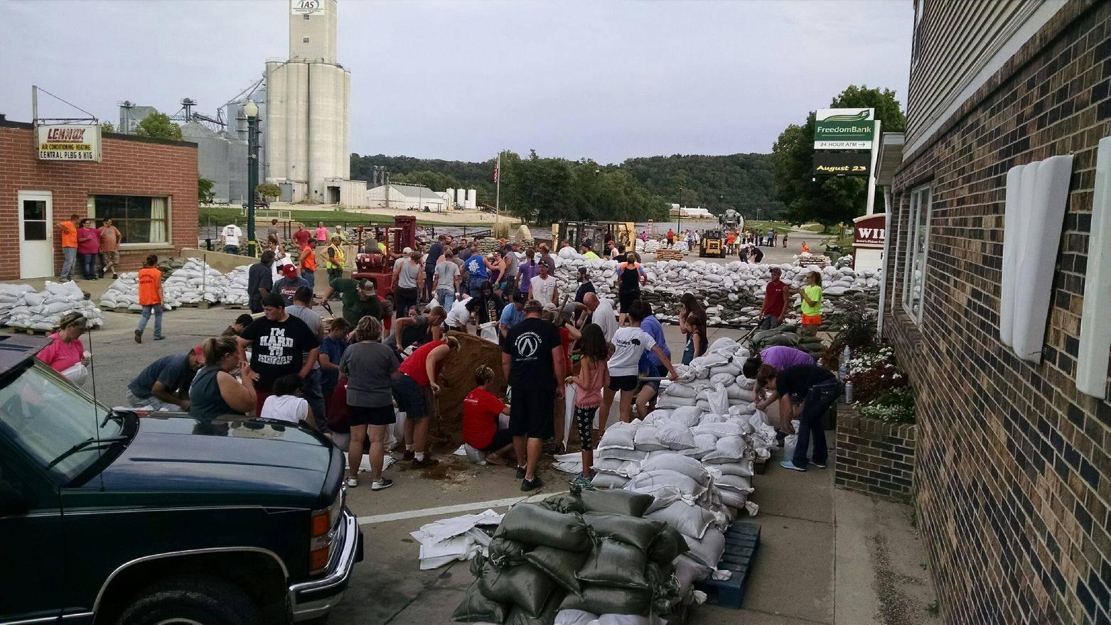 Elkader, Iowa residents build a sandbag wall to prevent flooding.
