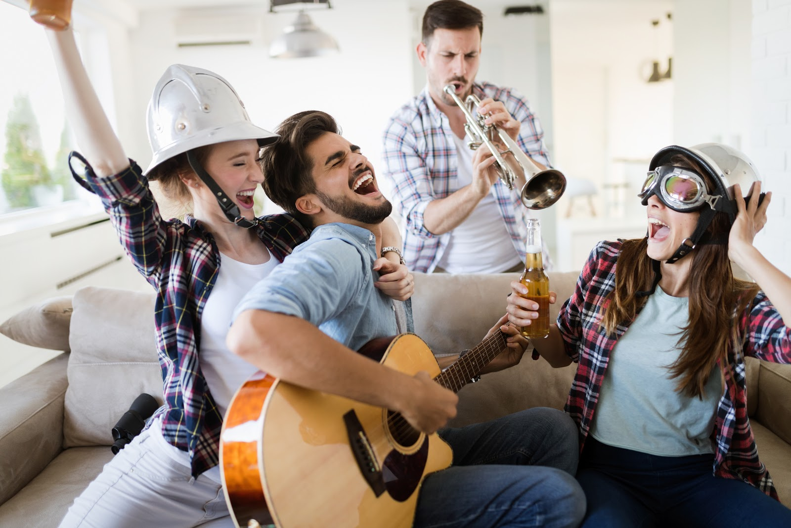 A group of people playing music, drinking been and laughing
