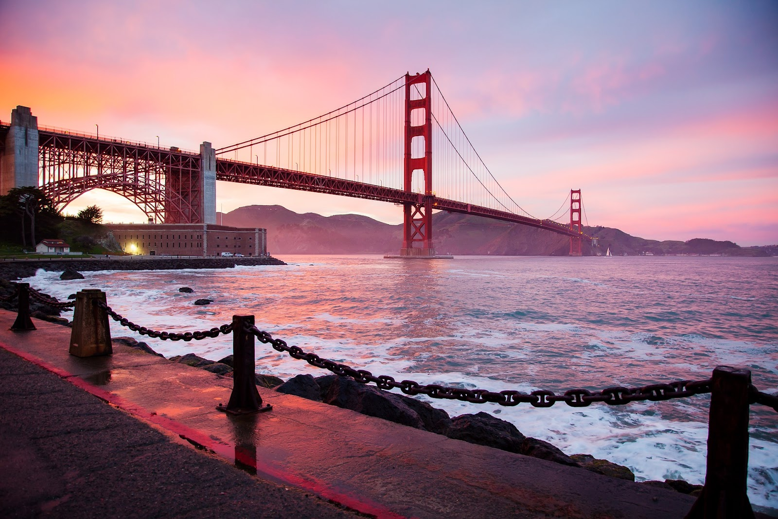 red golden gate bridge monument in san francisco with fenced path in foreground seen during sunset