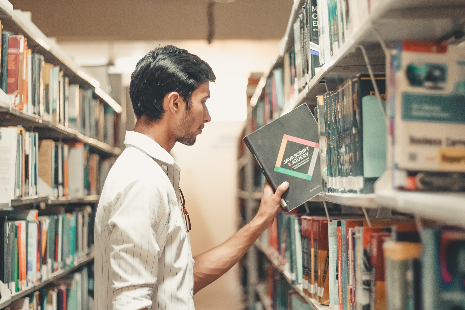 Documentation policy for MSPs, a man picking  a book of a bookshelf