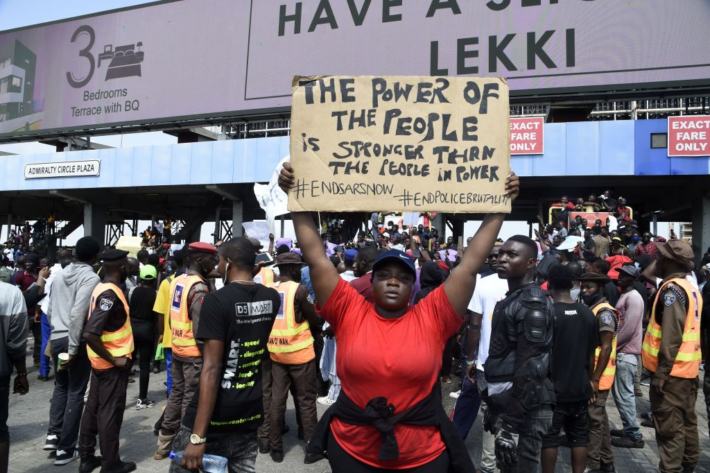 """Protestors at the Lekki toll gate. One    protestor can be seen holding up a sign with """"The Power of the People is stronger than the people in power"""" written on it"""