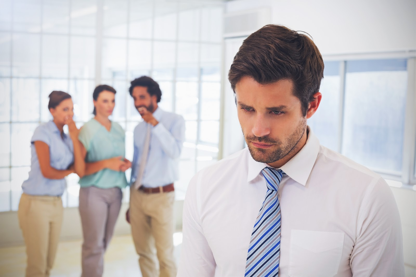 A man looking upset while coworkers whisper behind him