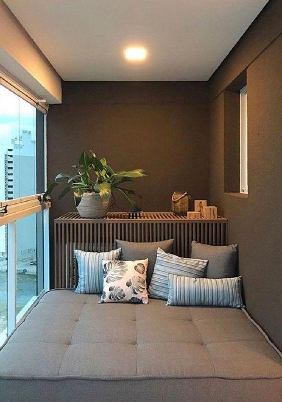 Varanda com sofá grande madeira aproveitando todo o espaço e bancada de madeira com vaso de planta.
