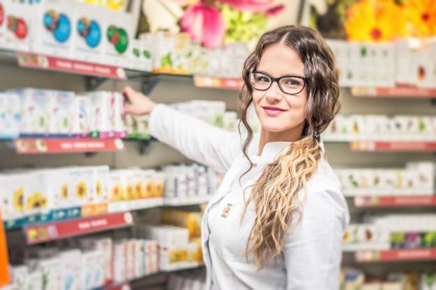 A imagem mostra uma atendente de farmácia em atuação enquanto sorri para a foto.