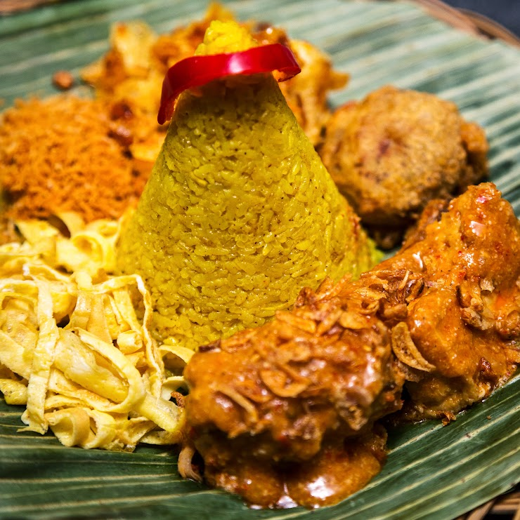 Nasi Kuning: Nasi kuning means yellow rice in English. In Indonesian culture, nasi kuning has favourable symbolic meanings. The yellow-coloured rice is perceived to look like a pile of gold, so it is often served in festive occasions; including parties, housewarmings, welcoming guests and opening ceremonies – as a symbol of good fortune, prosperity, wealth and dignity.Nasi kuning is quite widespread and commonly found in Indonesian culture. It can be found from Java to Sumatra, Bali and Sulawesi.Protein side can either be crispy fried chicken or beef rendang. Comes with side dishes including: twice-cooked mashed potatoes, cucumbers, sambal fried potatoes, sweet & spicy potato chips, shredded scrambled eggs, and coconut flakes.