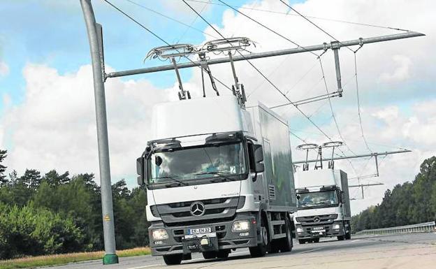 Dos camiones híbridos circulan con sus pantógrafos conectados a la catenaria./SIEMENS