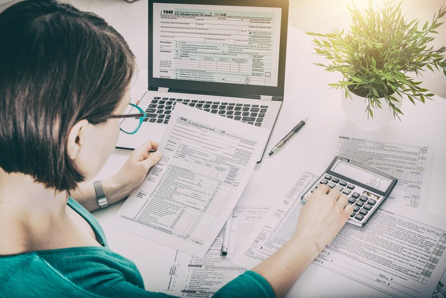 a woman at a desk working on tax forms