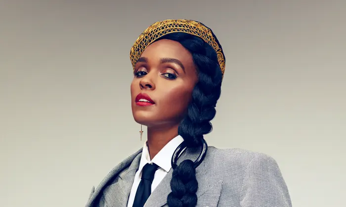 Janelle Monáe is wearing a gray suit with a white shirt and black tie. Her hair is in a braid draped over her shoulder and what looks like a gold Kente Kufi hat is on her head.