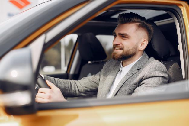 Homem sorrindo em seu automóvel