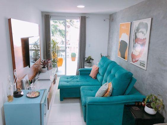 Sala estilosa colorida com sofá verde, frigobar azul, quadros decorativos e hack banca e marrom.