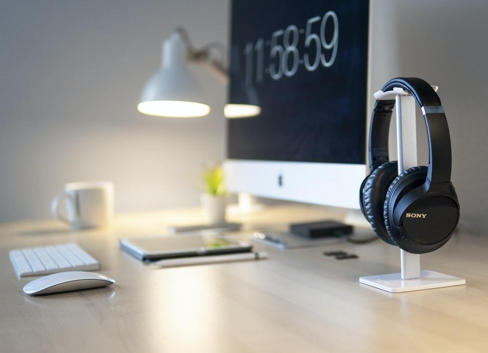 black Sony headphones beside iMac on top of table