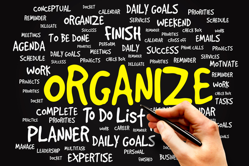 a word graphic centered on the word organize in bright yellow letter with other related words in white on a black background