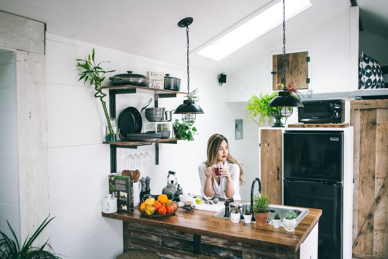 一個白衣女子坐在整潔的廚房中,手捧一個透明杯子。