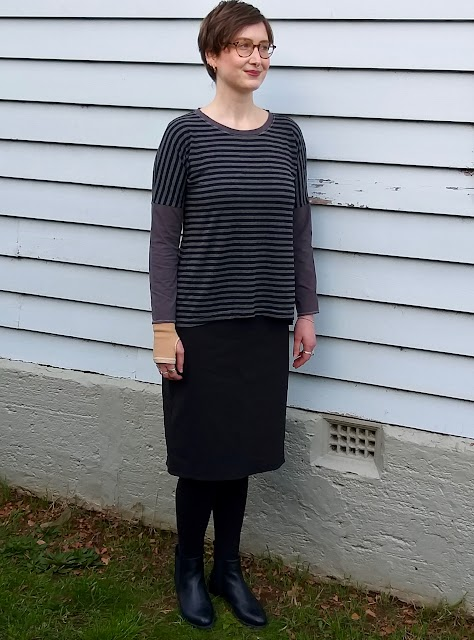 Siobhan stands in front of a weatherboard house. She wears a drop shoulder knit tee with grey/black striped body and concrete grey neckband and sleeves, with black straight knee length skirt, black leggings and ankle boots. She is smiling.