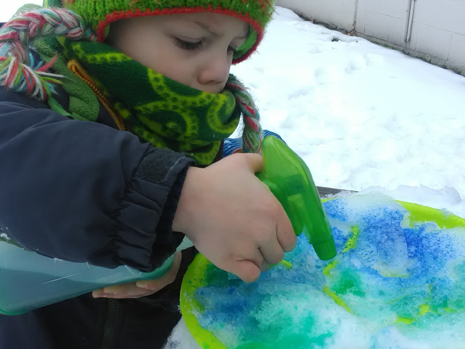 Small child spraying snow with colored water.