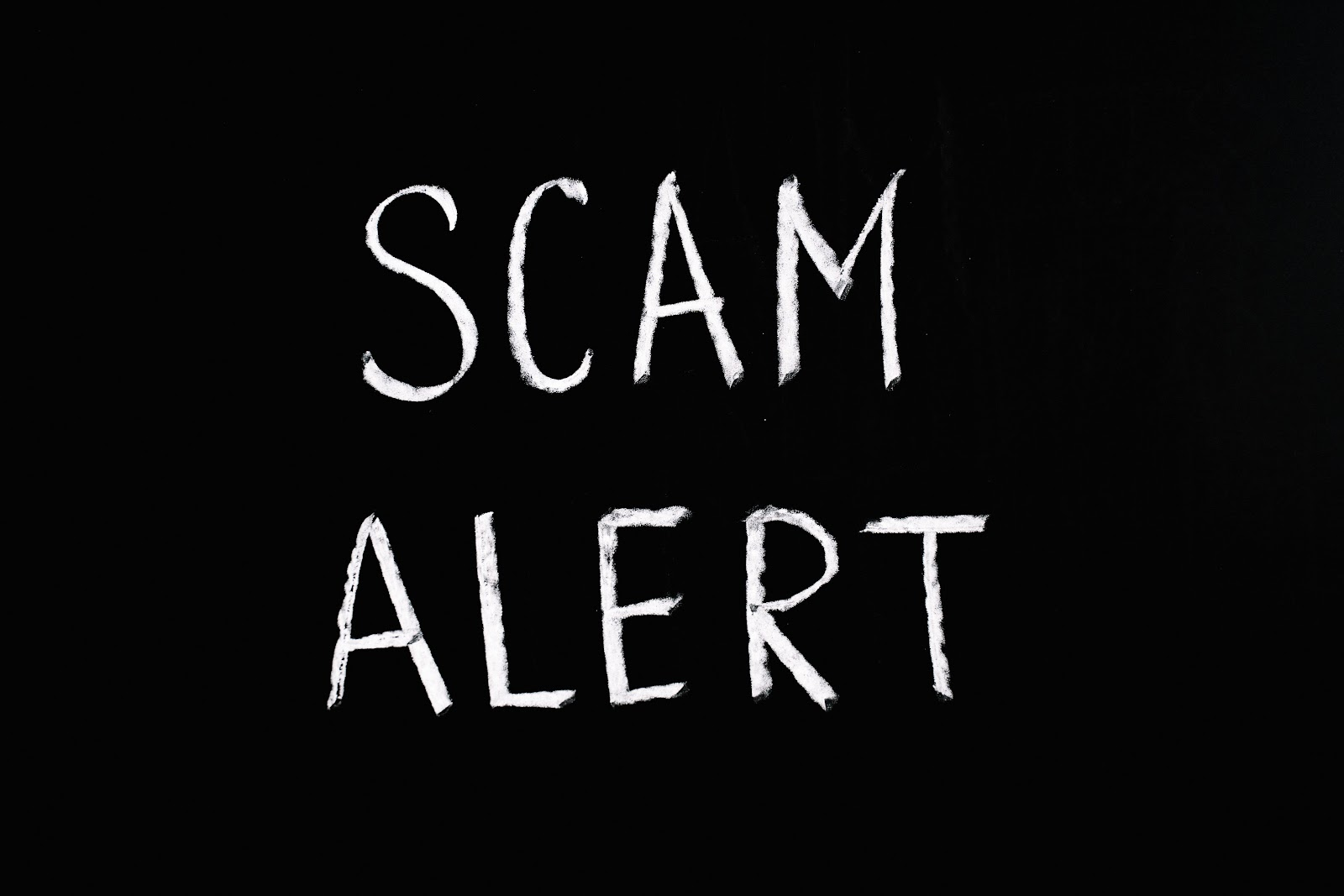 The words scam alert are written chalk style in white on a black background.