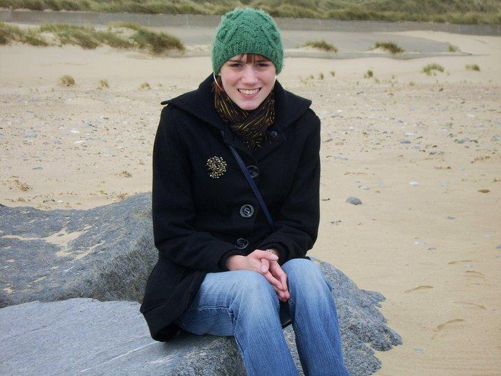 A photo of Jo, aged 21. She sits on a boulder on a beach, wearing a navy coat and a green cabled hat.