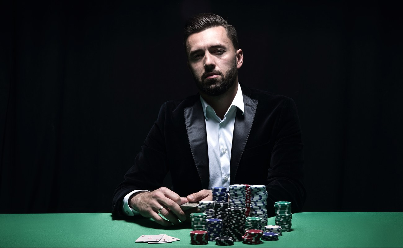Professional poker player at table with large stack of chips against a black background
