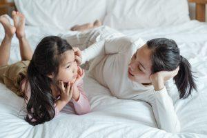 A mom and her daughter talking while lying on the bed