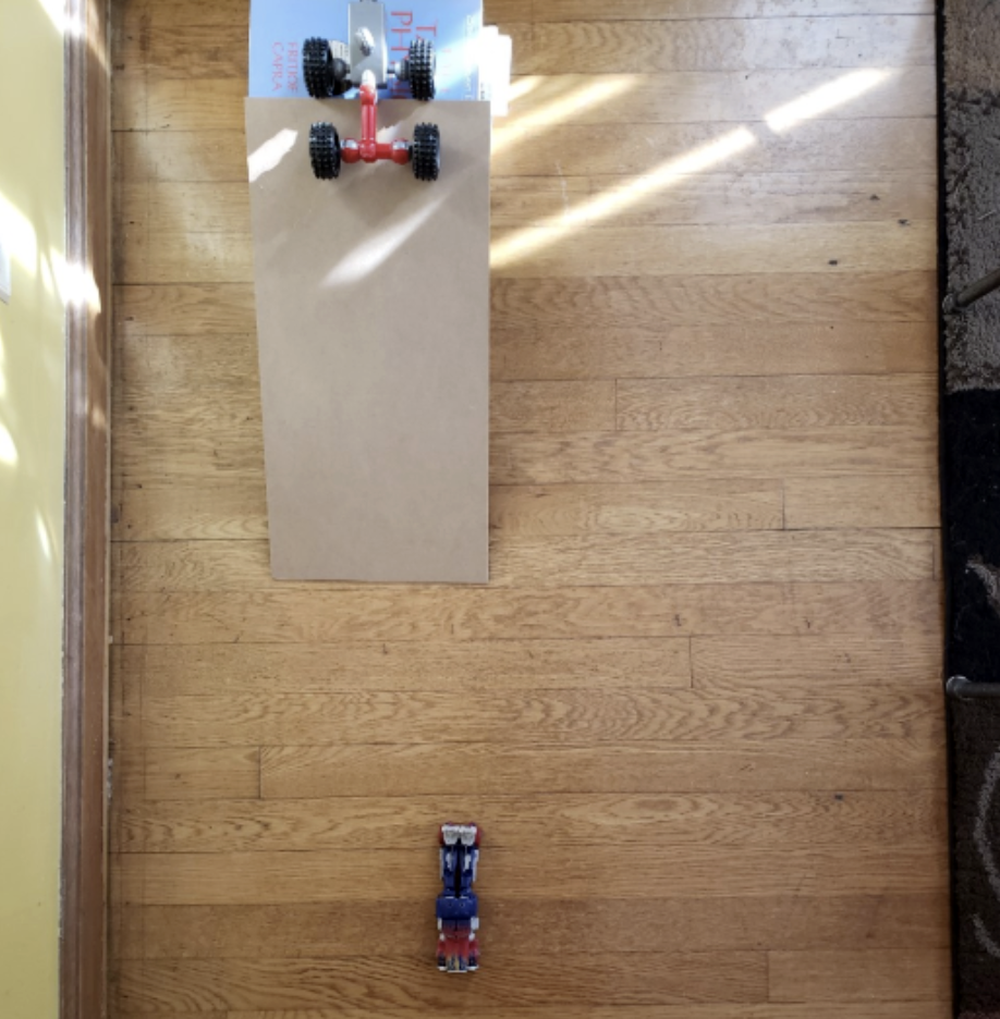 A toy car sits at the top of a ramp. Another toy car has already rolled down the ramp.