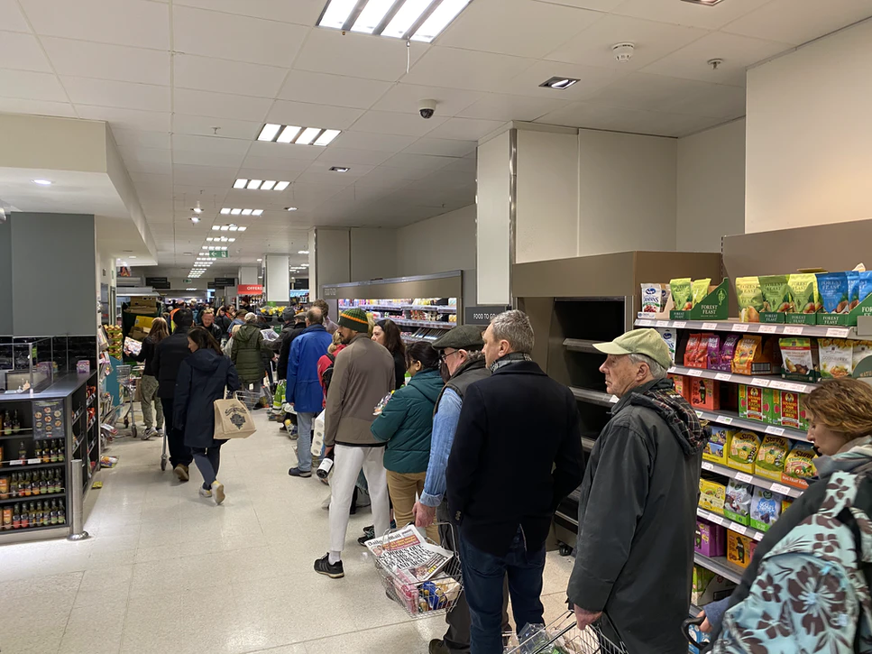 A long queue in a supermarket store with customers carrying their respective carts full of household items and groceries