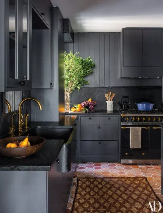 dark grey kitchen cabinets with black hardware black countertops and tile floor
