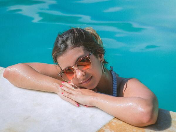 Foto de uma mulher na piscina apoiada na borda.