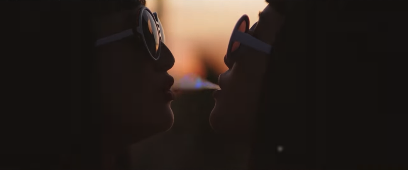 Two people's faces are close together in twighlight. They both are wearing white sunglasses and one blows smoke into the others mouth.