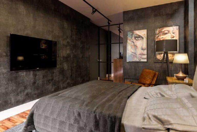 Quarto de casal com paredes em cimento queimado, detalhes preto e quadros decorativos.