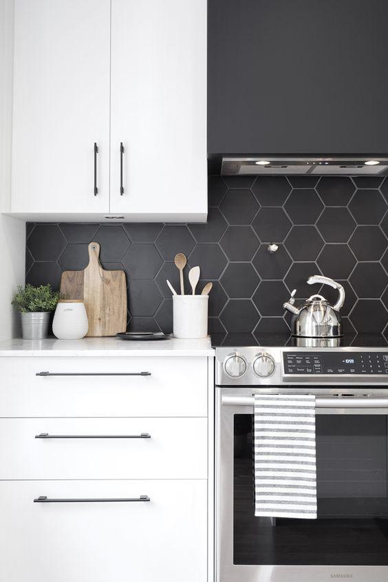 Cozinha com armários brancos, eletrodomésticos de inox e parede da pia com revestimento hexagonal preto