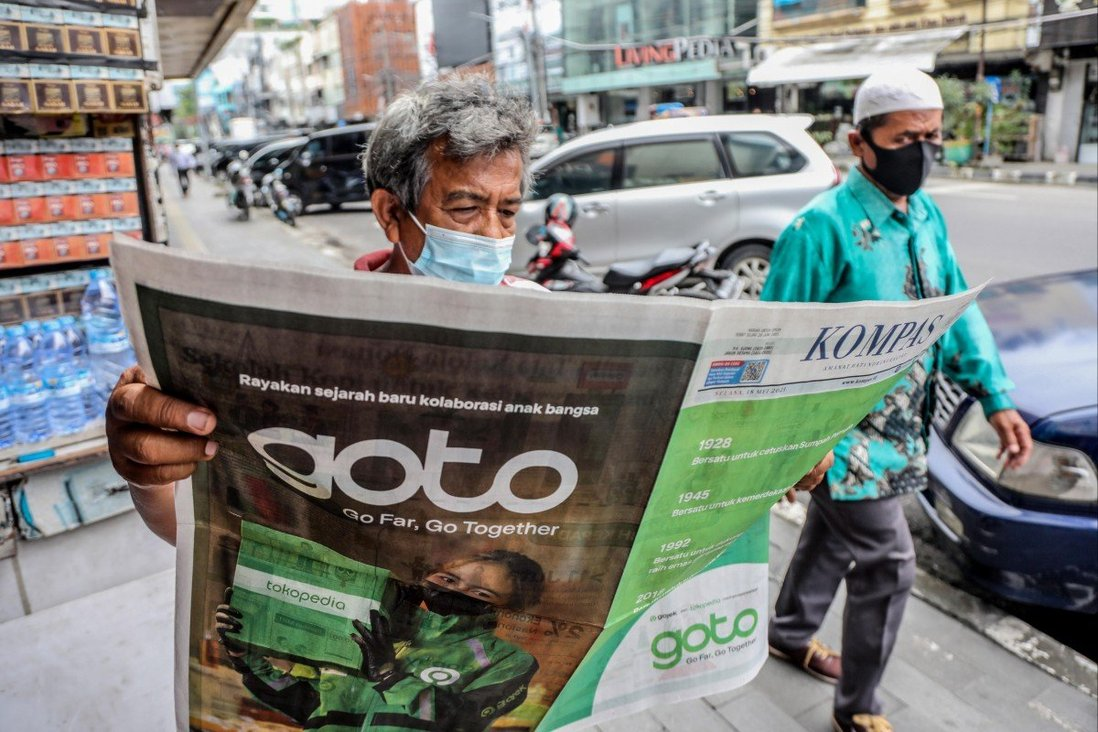 A man reads a newspaper with an advertisement of the Gojek-Tokopedia merger in Medan, Indonesia, on May 18. The resulting multibillion-dollar company, GoTo Group, is an emerging player in Southeast Asia's fintech space. Photo: EPA-EFE