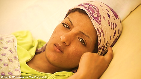 Shackled: Nisreen Mansour al Forgani lies in a hospital bed after admitting executing as many as 11 rebel prisoners