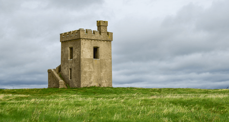 a tiny castle all alone on an empty landscape with grey skies