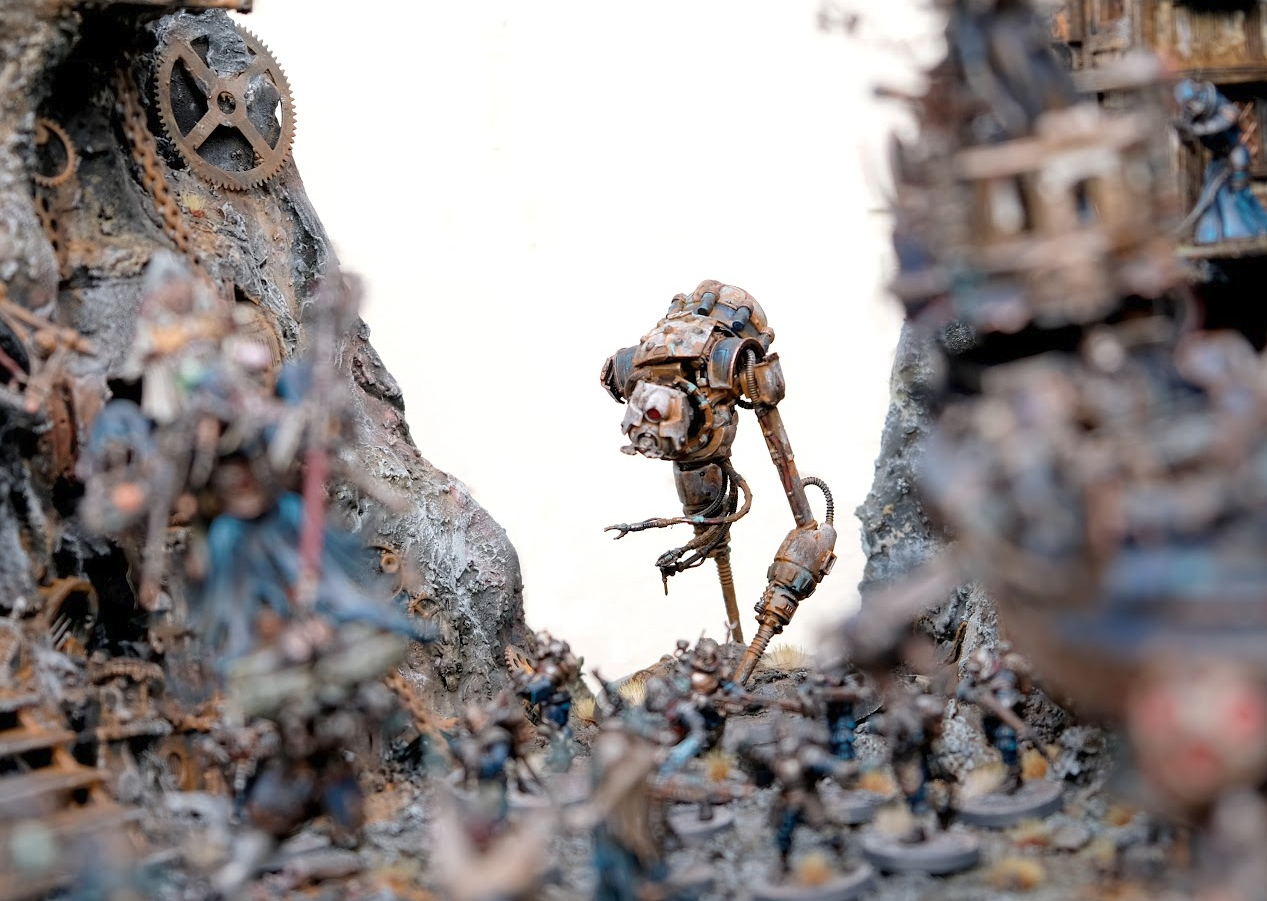 A tall robot on long striding legs is in focus at the back of an army diorama