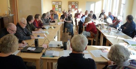Konferenzteilnehmerinnen und Konferenzteilnehmer am Konferenztisch.