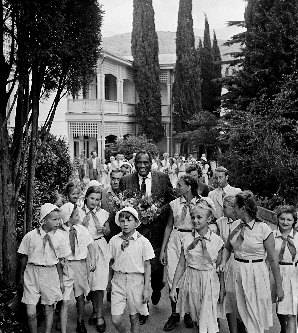 Russian kids greeting American singer and Lenin Peace Prize winner Paul Robeson with flowers.
