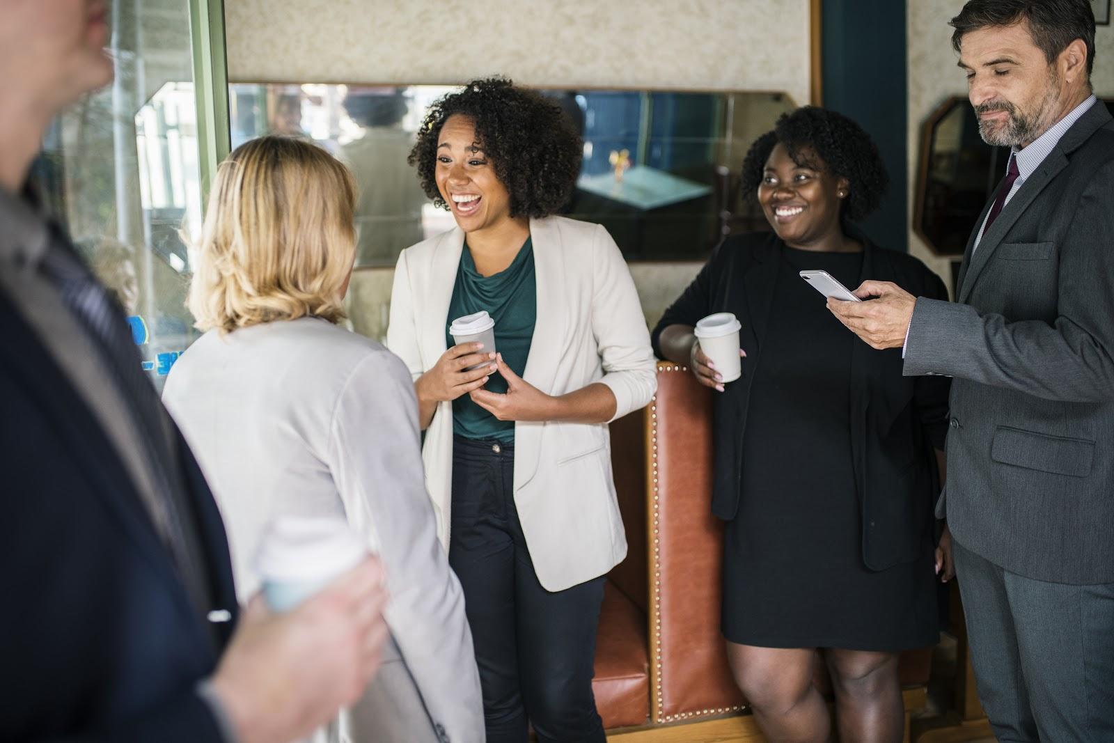 Quatro pessoas conversando descontraídas no ambiente de trabalho.