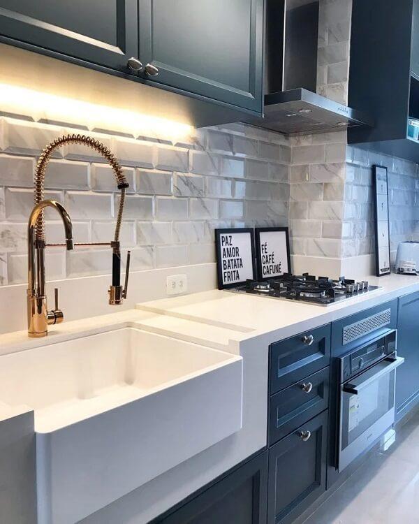 Cozinha com armário preto com bancada branca, torneira dourada, azulejo do metrô na cor branca com estampa marmorizada.
