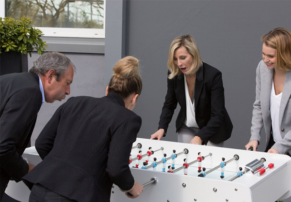 Employees Playing Football Table Game in Office