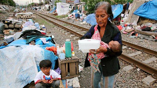 Sumarni (73) bersama dua cucunya menyantap makanan seusai pulang dari kebaktian Natal di pinggir rel kereta api di kawasan Tanah Tinggi, Kecamatan Johar Baru, Jakarta Pusat, yang digelar pada Kamis (17/12), lebih cepat sepekan dari libur Natal.