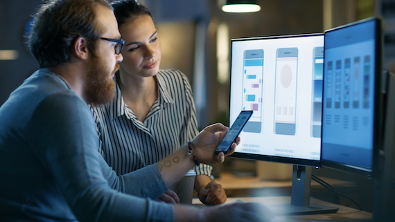 Web application development: Two people looking at mockups on computer