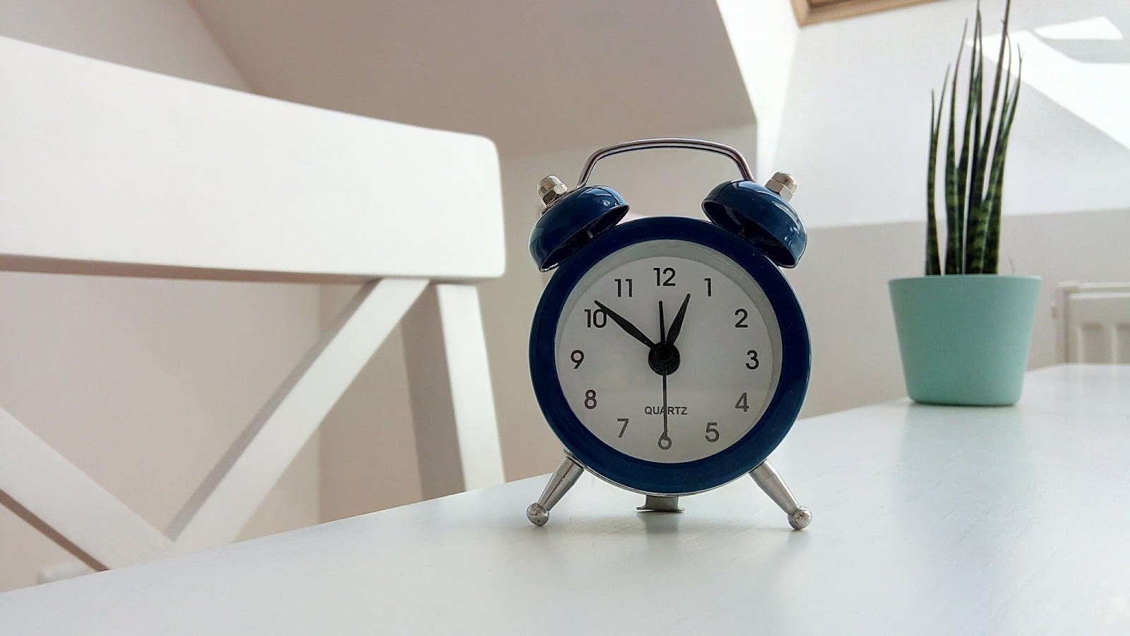 Photo of a basic alarm clock on a bedside cabinet