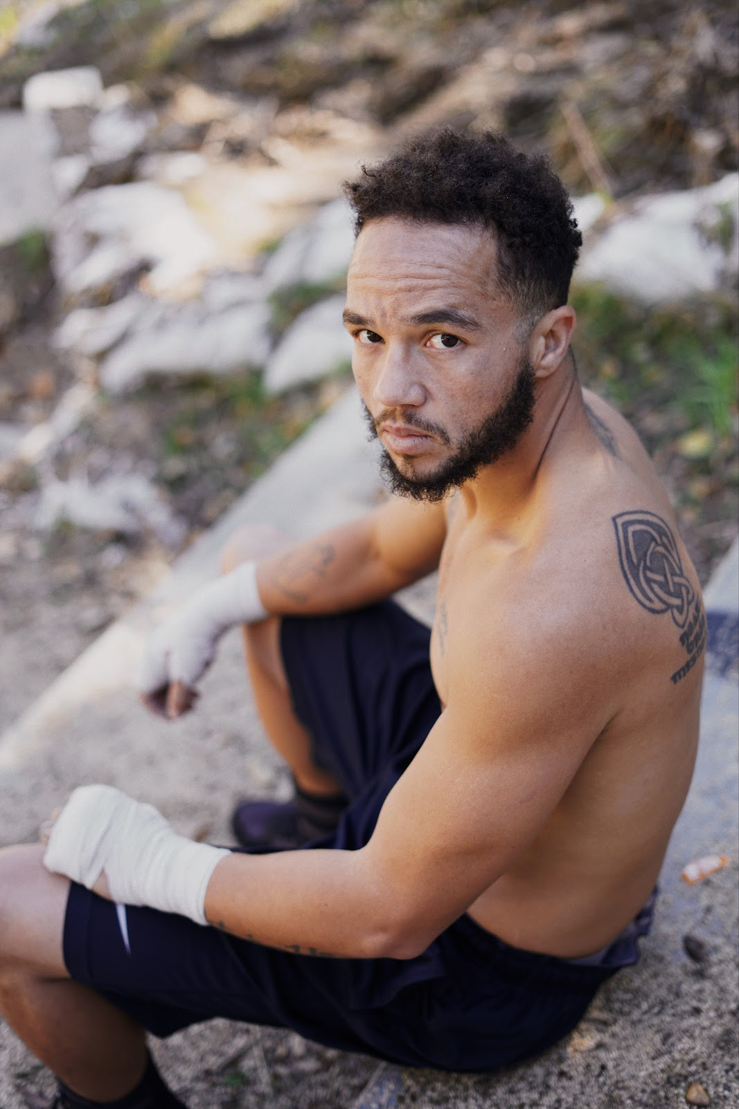 "A light brown-skinned man sits outside and looks up and to the left at the camera. He has short curly black hair and a short black beard and mustache. He's a boxer, shirtless, hands taped, wearing boxing shorts. The expression on his face is somehow both kind and forbidding, the epitome of ""Don't start no shit, won't be no shit."" You can see part of a Celtic knot tattoo on his back."