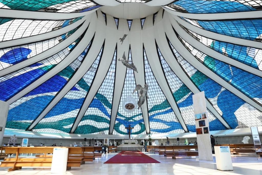 Fotografia do interior da Catedral. A cobertura, com vitrais em tons de azul e verde, cria uma visão única que contrasta com a passagem escura da entrada.