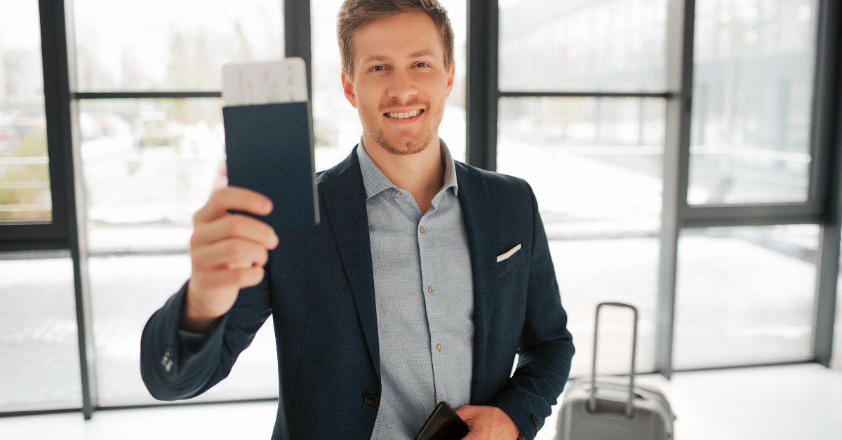 A man with his suitcase showing his passport and boarding pass