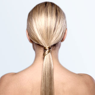 A woman's blonde hair in a low ponytail at the nape